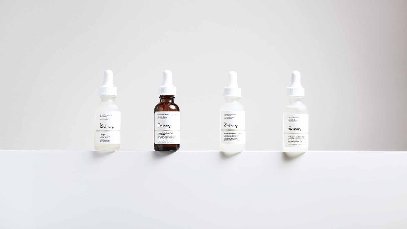 Four of The Ordinary products on a narrow white ledge with a white background