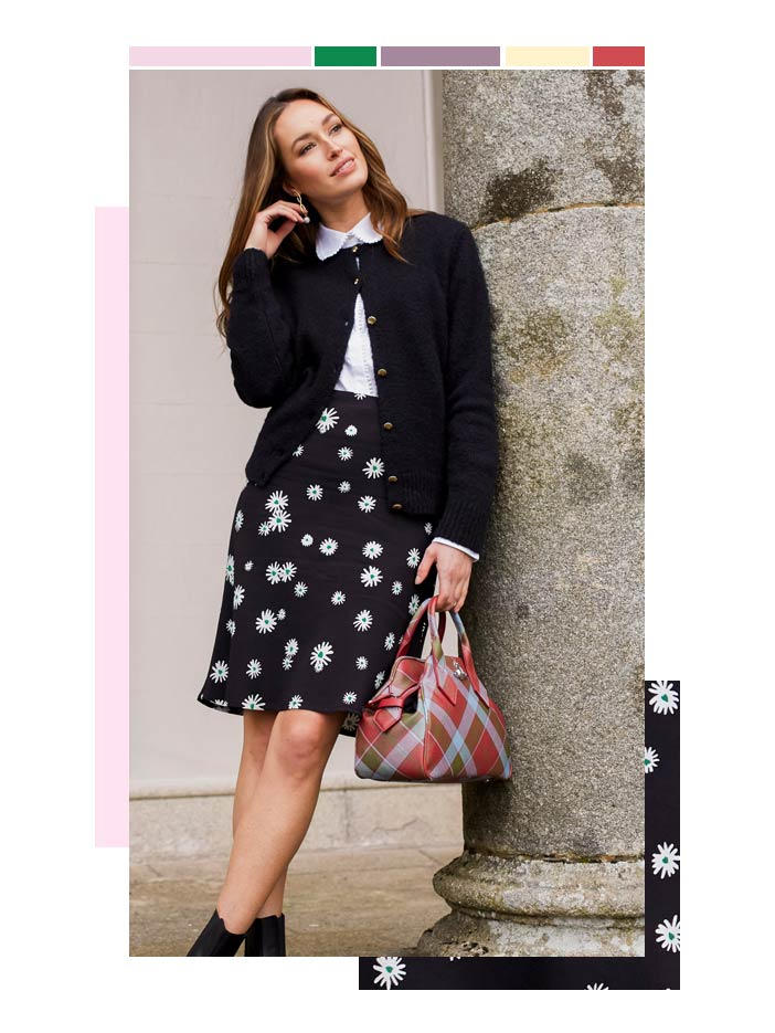 Model leans against pillar weaing a monochrome outfit including a black skirt with whit and green floral print