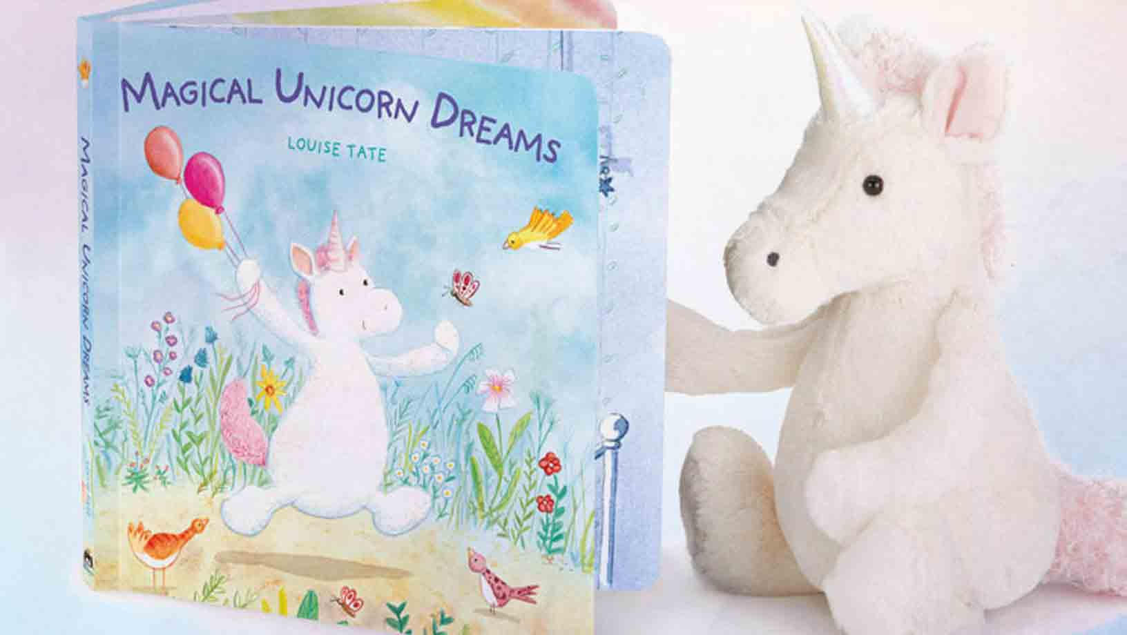 Magical Unicorn Dreams Book with a happy unicorn dancing along holding baloons behinf him with birds and a butterfly around him shout beside a soft pink and white unicorn teddy.