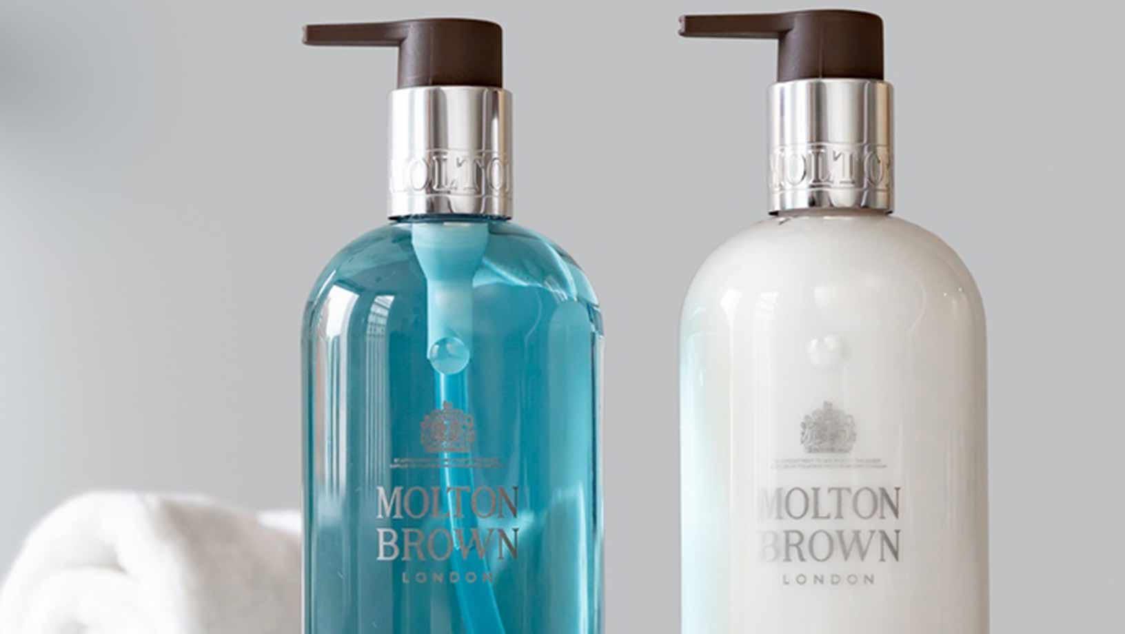 Two Molton Brown London products, one handwash in blue, one hand lotion in white with a white towel in the background