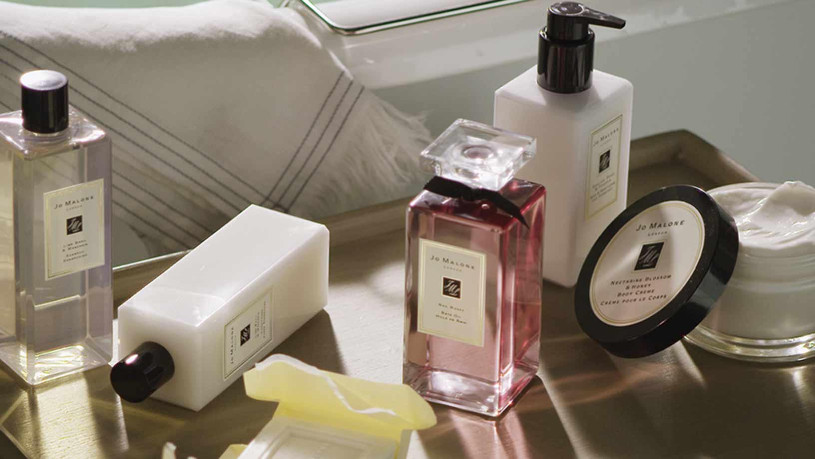 Five Jo Malone London products on a wooden side table including body wash, body cream and perfume