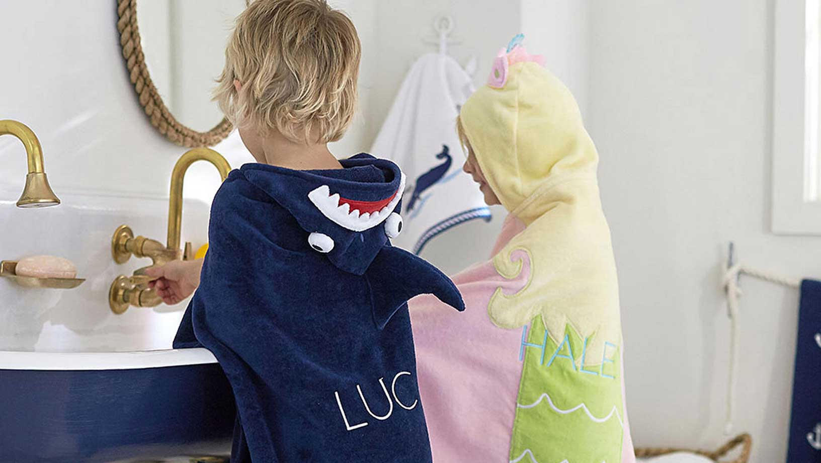 A young boy and girl wearing Pottery Barn Hooded Towels while washing their hands at a navy and white skink. The boy wears a navy towel with a skark on the hood and the girl wears a pink yellow blue and green towel with a unicorn on the hood.