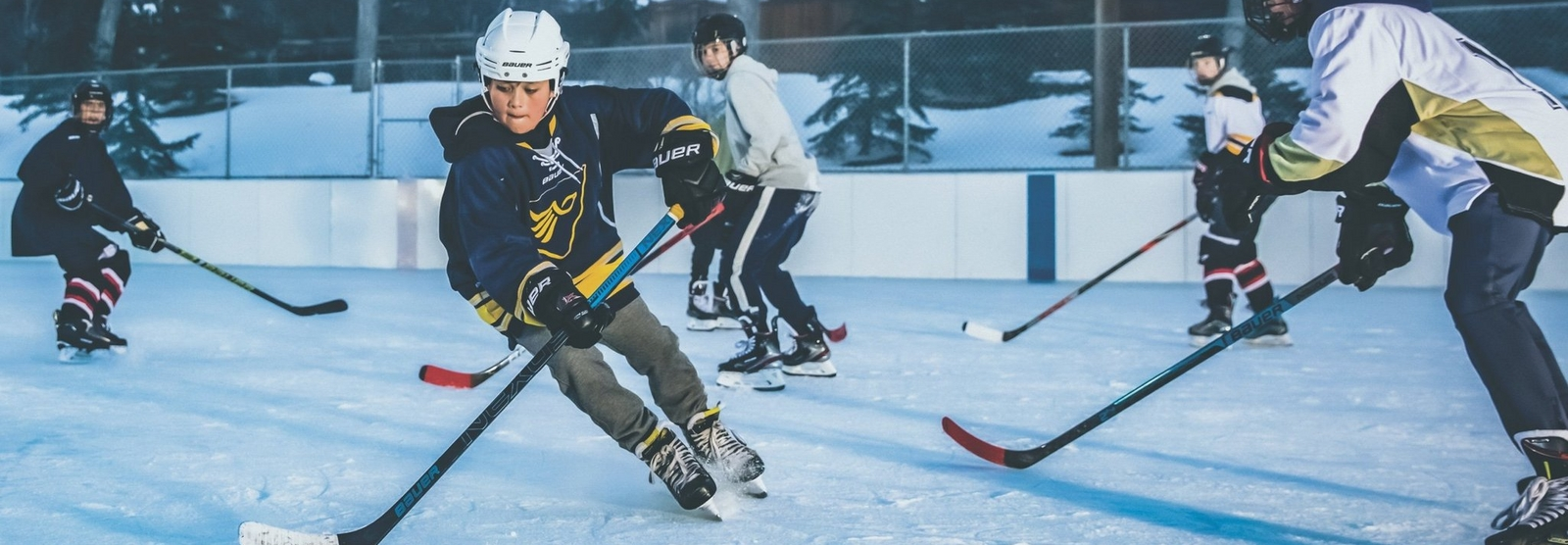 Kids playing hockey on ice.