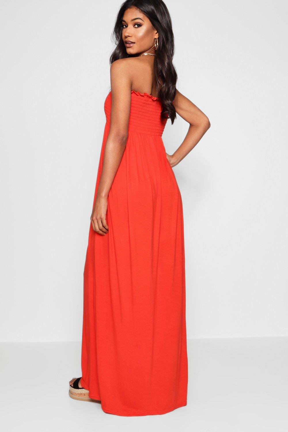 A lady wearing a red bandeau style maxi dress.