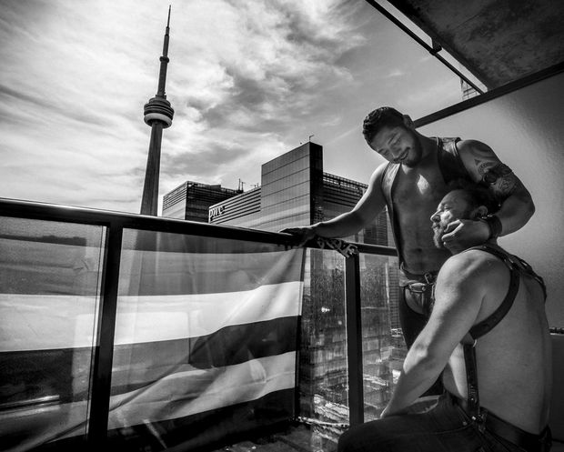 Muddy York Rugby Football Club player Danny Perez (standing) and his partner Jonathan Buckley cuddle on the balcony of their apartment in Toronto, Canada