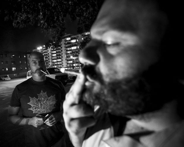 Muddy York Rugby Football Club's players Carlo Vitelli (right) and David Cameron-Donnachie smoke outside the Phoenix club in Toronto.