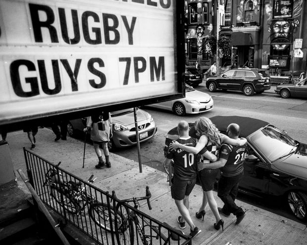 Muddy York RFC's captain Jimmy Karttunen (left) and teammate Carlo Vitelli (right) walk with drag queen Demanda Tension along Church Street in Toronto's gay village.