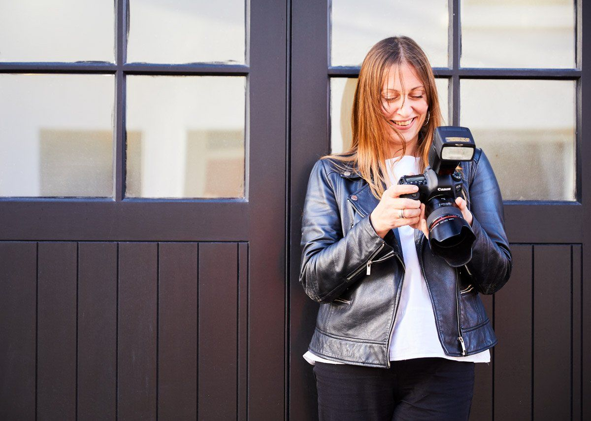 Female wearing leather black jacket outdoors holding a Canon 6D Mark II + Canon Speedlite 470EX-AI