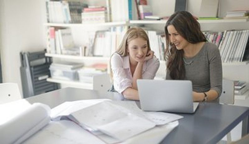 Two women working in front of a laptop