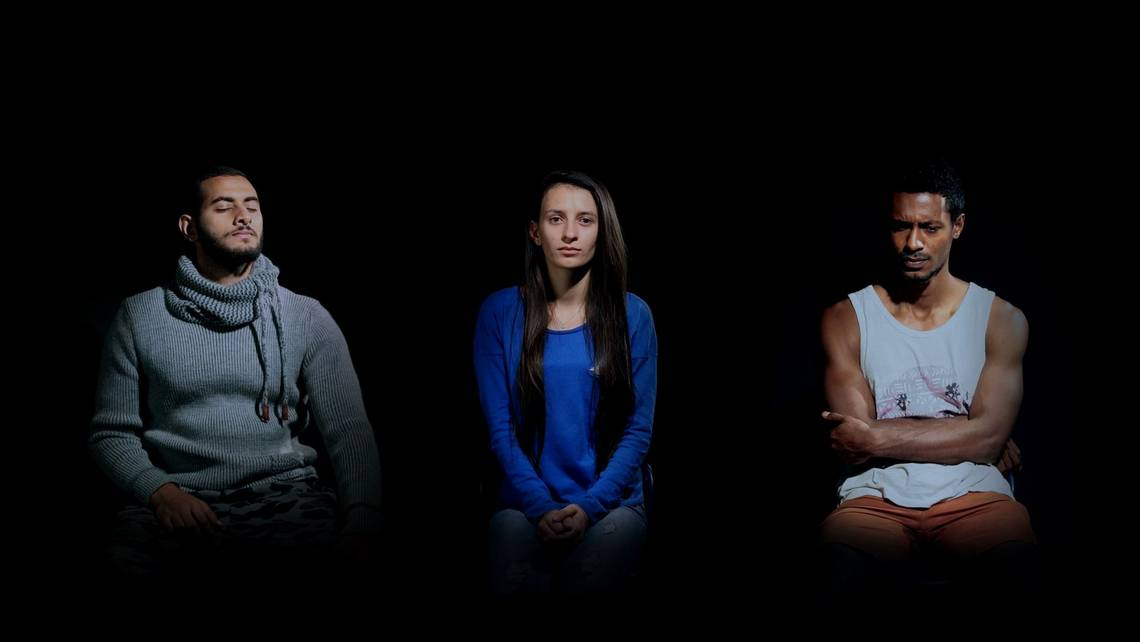 Video still of a man with his eyes closed, a woman looking neutral, and a man with arms folded, frowning. Filmed on a Canon EOS 5D Mark IV.