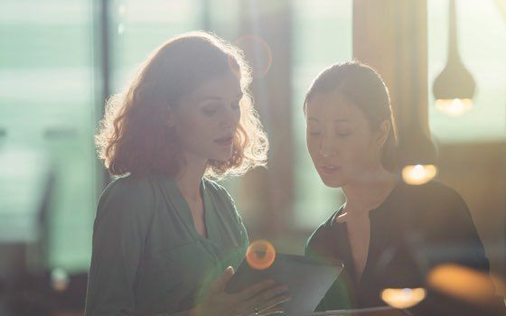 Two women in soft focus look over a tablet device as downlights glimmer in the foreground.