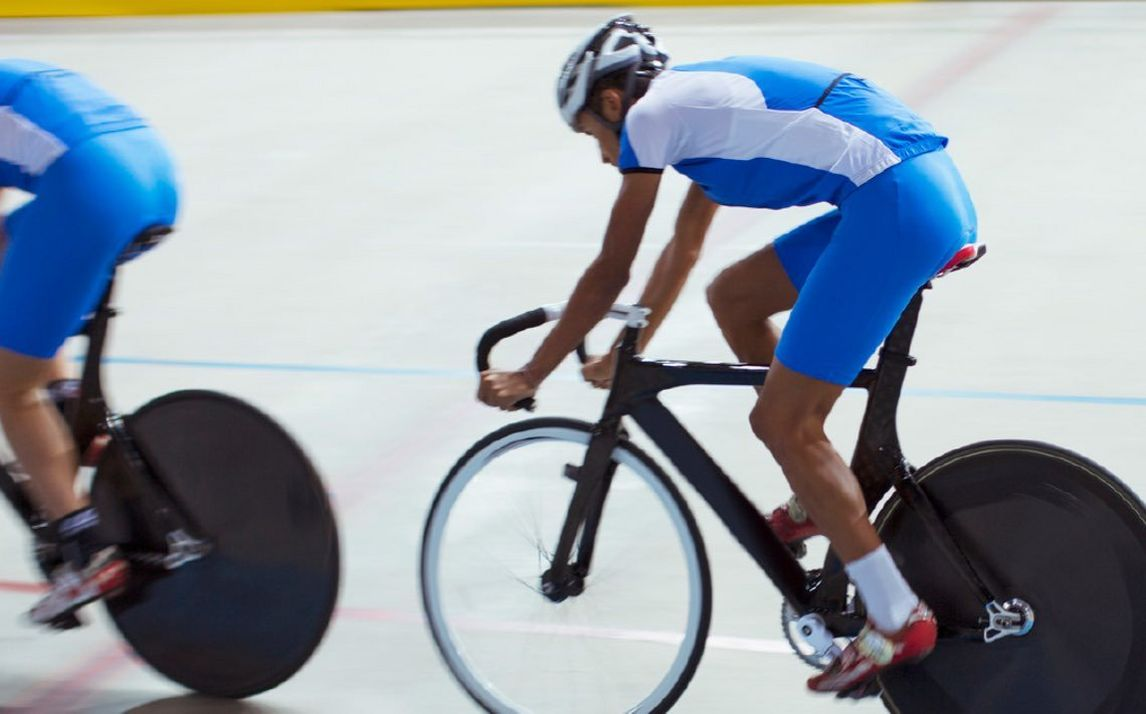 Two professional track cyclists in blue and white kit ride wheel-to-wheel as they compete in the velodrome.