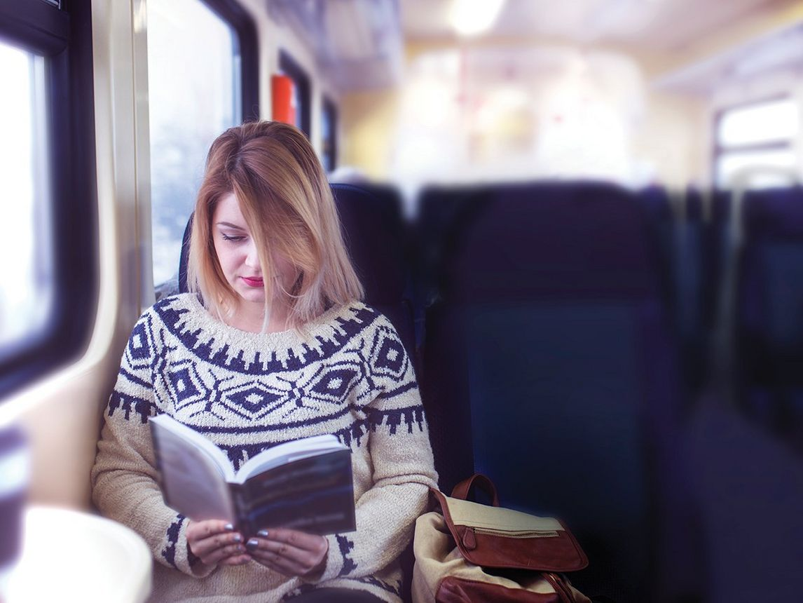 Young woman reading book on train