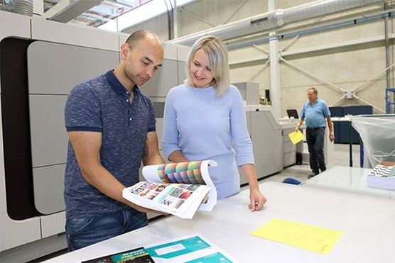 Two print professionals looking at colourful booklet printed from the VarioPrint i300