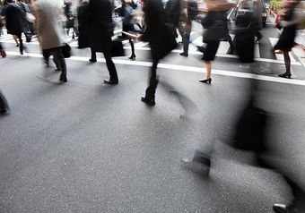 People walking down a street, some are blurred