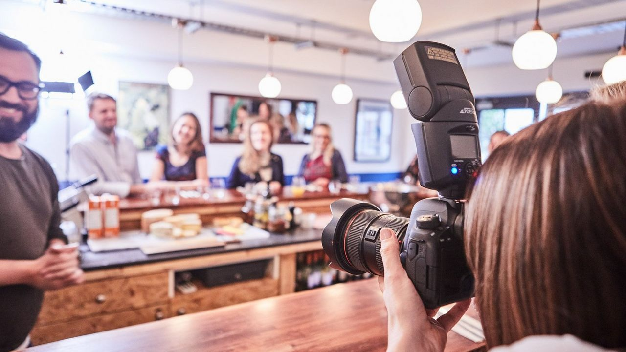 Female taking a group picture in a restaurant with a Canon 6D Mark II + Canon Speedlite 470EX-AI