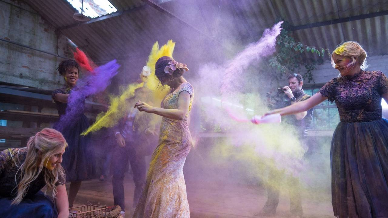 fun action picture of two woman pouring powder paint on each other