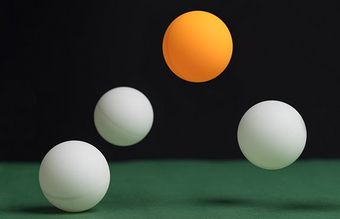 Balls bouncing on a table, one is orange the rest are white