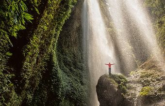 Man with his arms outstretched stood on a rock underneath a waterfall