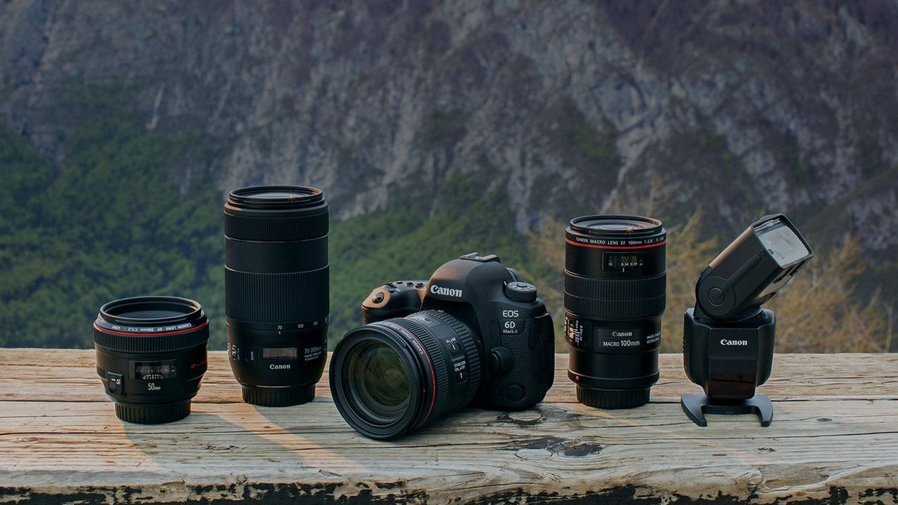 Canon range of EOS camera and lenses with a mountain background