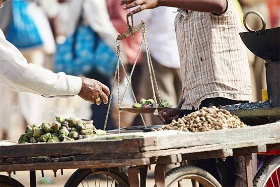 Men balance produce on weighing scales in a market