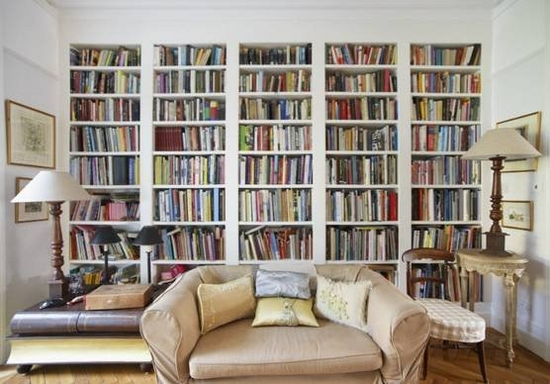 Living room with a colourful bookcase across the back wall