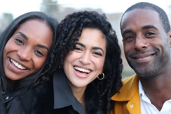 A close-cropped portrait of three smiling people with the background blurred behind them.