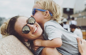 A mother picks her son up to hug, both of them wearing sunglasses.
