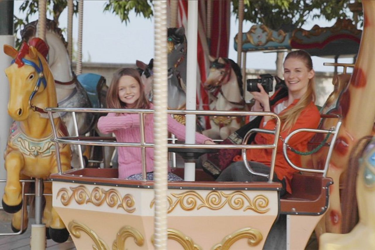 A woman with a Canon EOS 250D rides a carousel with her daughter.