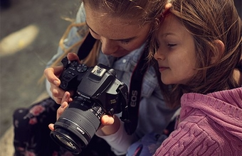 Two children looking through the viewfinder of a camera.