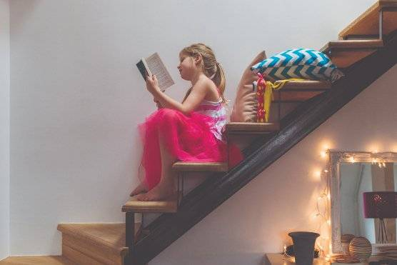 A young girl sitting reading a paperback book on some stairs