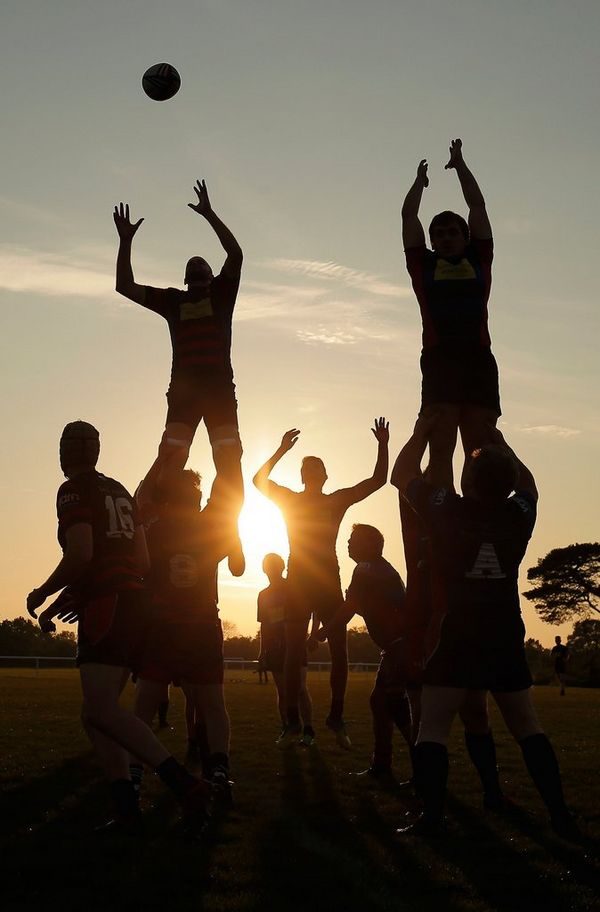 Silhouette of rugby players jumping for a ball at sunset. Photo by Tom Jenkins.