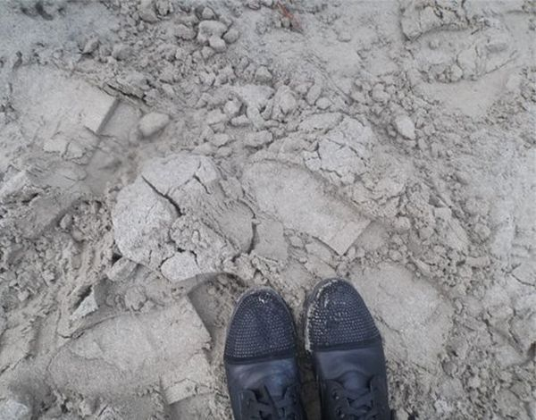Feet in black shoes, stood on a dusty clay surface.