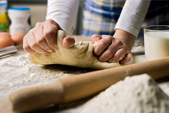 Close up of person kneading dough