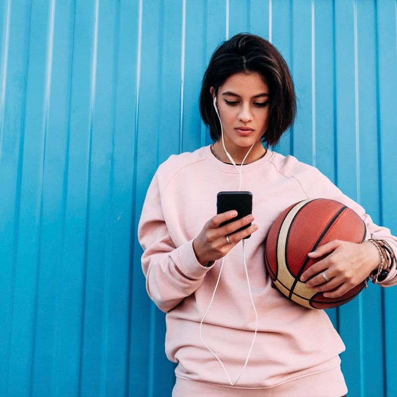Woman with basketball in front of blue wall