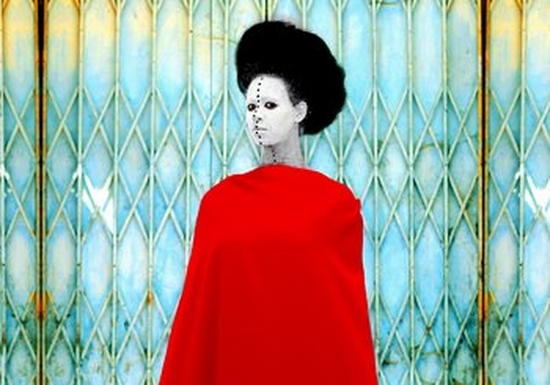 A woman stands in front of a rusting security grille. She wears a dramatic red cape, which covers her from the neck down, and her head is framed by a halo of black hair. Her face is painted white and a line of black dots stretches from the top of her forehead to the base of her neck, which are inspired by traditional African body art.