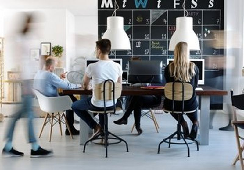 A modern office environment, with a chalkboard wall as a team calendar, plants and natural light. Employees sit around a dining style table, wearing jeans and t-shirts.