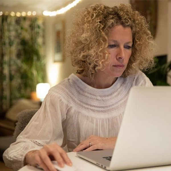 A blonde, curly-haired woman sits at a laptop.
