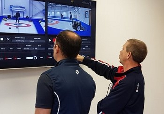 Two men in athletic wear look at a split screen showing two views of curling players on the ice.