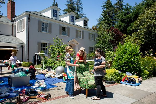 Three women talk at a garage sale in front of a large house. Photo by Laura Morton.