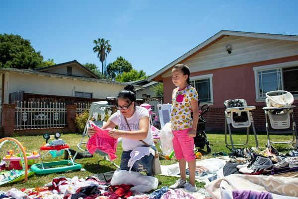 A woman and her daughter look at clothes at a garage sale in the garden of a smaller home. Photo by Laura Morton.