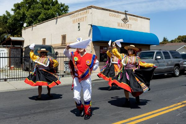 Four dancers in traditional Mexican dress perform in the middle of a street. Photo by Laura Morton.