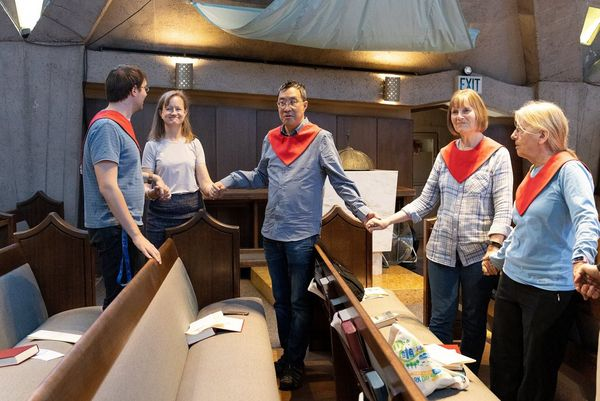 Five congregants with red neckties stand holding hands at church. Photo by Laura Morton.