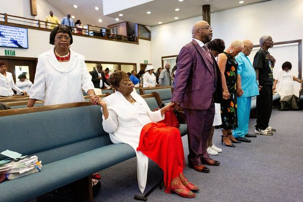 Congregants stand holding hands at church – one woman sits with a red shawl across her knees. Photo by Laura Morton.