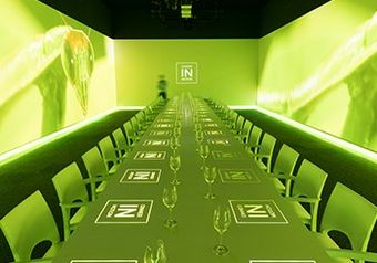 A long dining table, bathed in green light with the Dinner in Motion logos projected onto it.