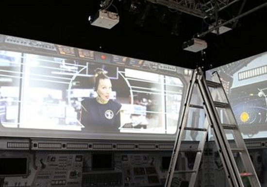 A ladder and projectors pointing to a screen, where a woman in a headset is broadcast.