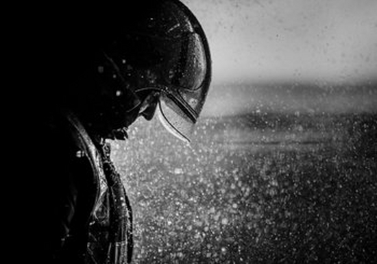 A black and white photo of a man in a helmet. He stands to the left of the image, with rain pouring down in front of and on him.
