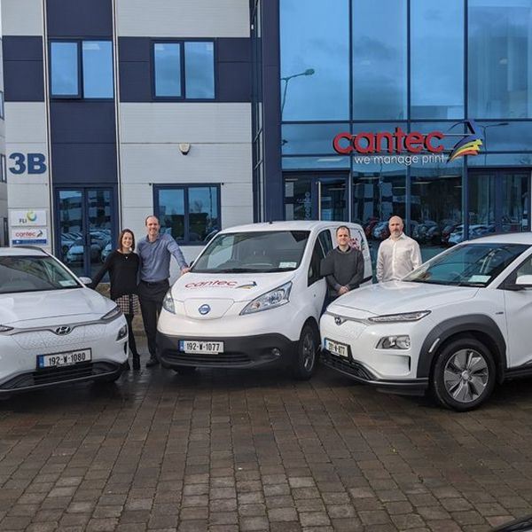 Two white electric cars and an electric van, with three men and a woman standing with them. Behind them are the offices of Cantec Ireland.