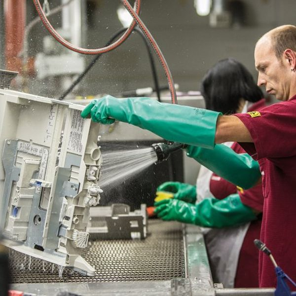 A man in a deep red shirt and green, elbow length rubber gloves, is in an industrial setting and cleaning a section of a machine using a powerful water spray.