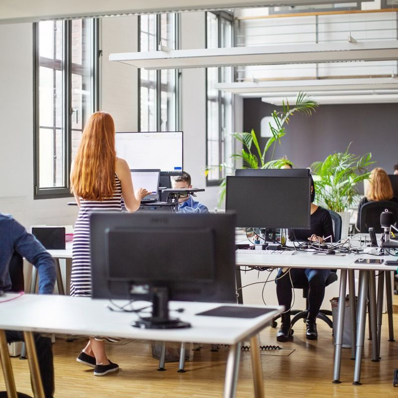 Woman with long ginger hair works at a standing desk amongst colleagues